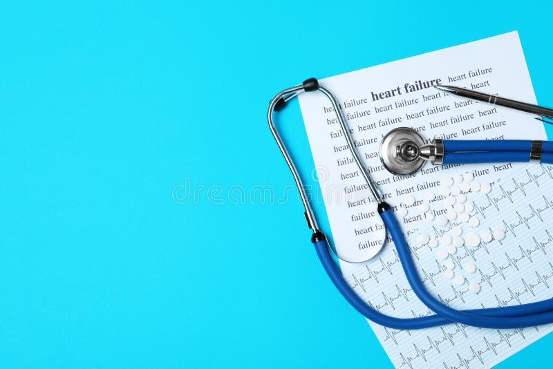 Plan lekmanna- sammansättning med stetoskopet, FEL för ord HJÄRTA och kardiogrammet på färgbakgrund arkivfoto