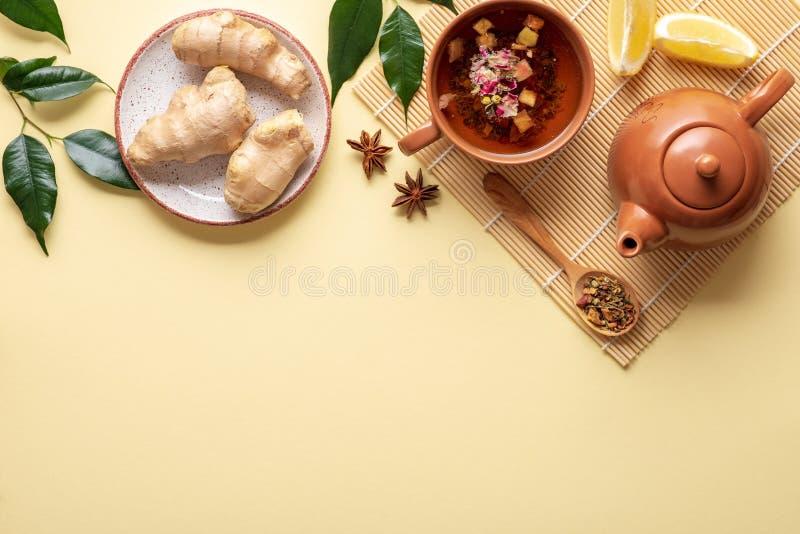 Plan lekmanna- sammansättning med tekoppen, tekanna på matt bambu, sked av torkat te, ingefära rotar i plattan, filialer med grön royaltyfria foton