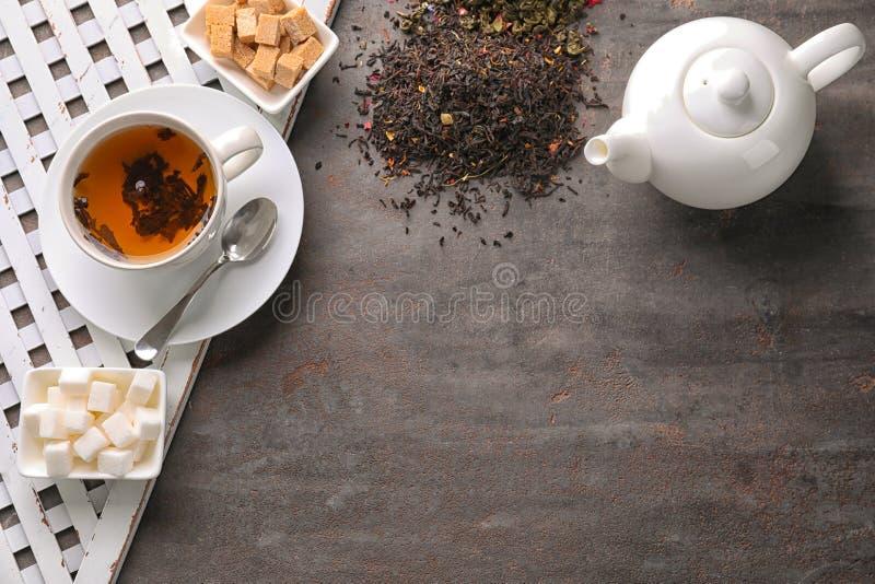 Plan lekmanna- sammansättning med torra teblad, socker och den varma drycken på grå bakgrund arkivbild