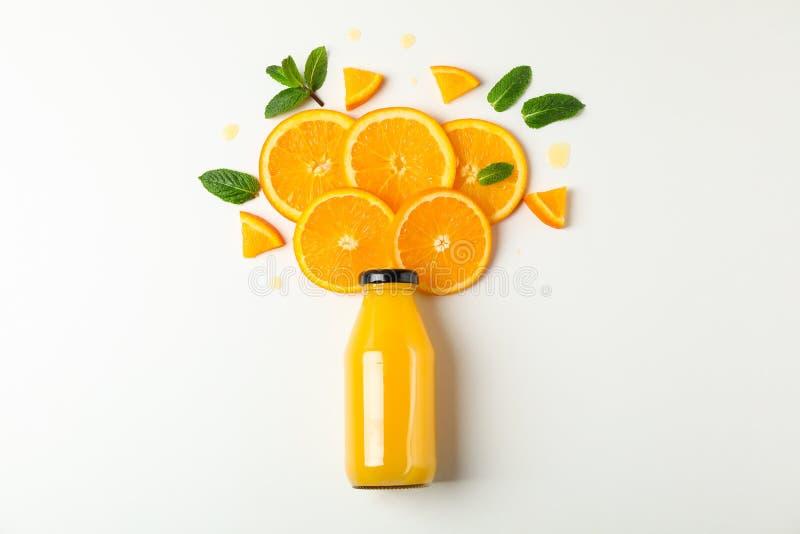 Plan lekmanna- sammans?ttning med orange fruktsaft i flaska, orange stycken och mintkaramellen p? vit bakgrund, utrymme f?r text royaltyfria bilder