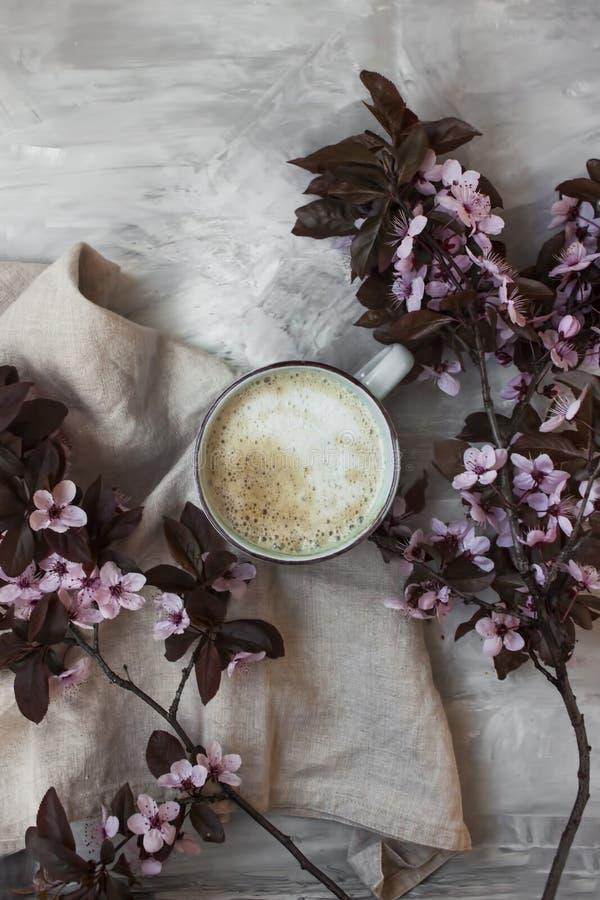 Plan lekmanna- sikt av pastellfärgade rosa blommor bredvid en varm kopp kaffe royaltyfri fotografi