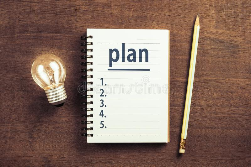 Plan Lists and Idea. Plan lists on notepad with glowing light bulb, goal setting idea stock photos