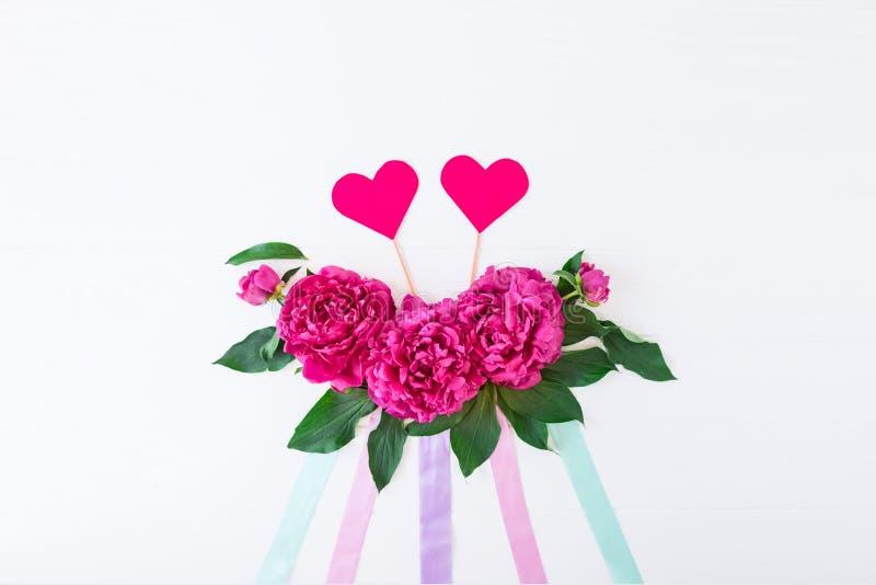 Plan mit Pfingstrosenblumenzusammensetzung, B?ndern und zwei Herzen auf einem wei?en Hintergrund Liebe, heiratend Das Blumenmodel lizenzfreies stockbild