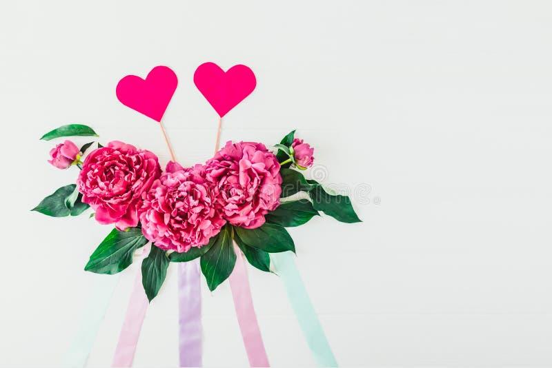 Plan mit Pfingstrosenblumenzusammensetzung, B?ndern und zwei Herzen auf einem wei?en Hintergrund Liebe, heiratend Das Blumenmodel lizenzfreie stockfotografie