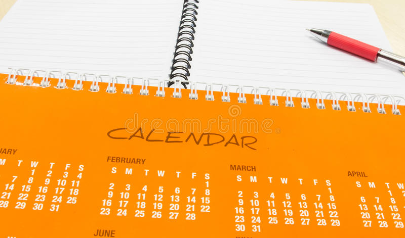 Plan pendant la nouvelle année, calendrier orange avec le stylo et carnet sur le bureau images stock
