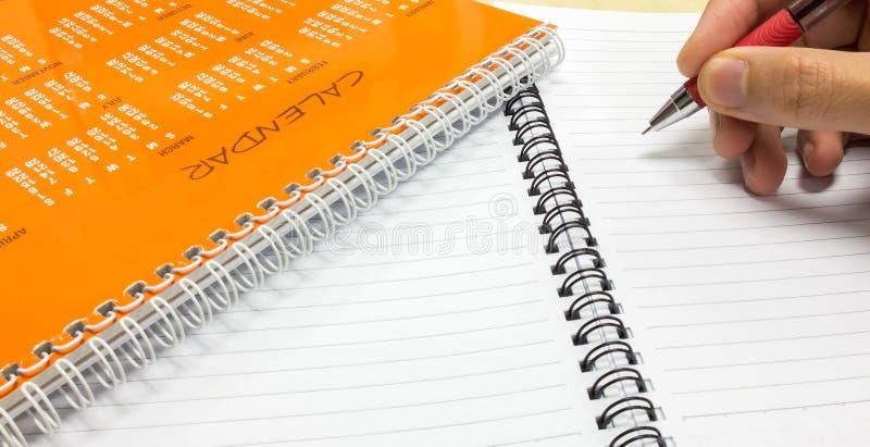 Plan por Año Nuevo, calendario anaranjado con la pluma de tenencia del hombre y cuaderno en el escritorio de oficina imagenes de archivo