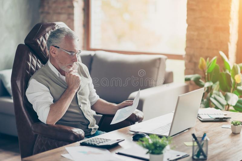 Plan profit paper cost debt credit bill success tax people armchair chair freelance company owner concept. Side profile view. Photo of serious pensive analyzing stock photo