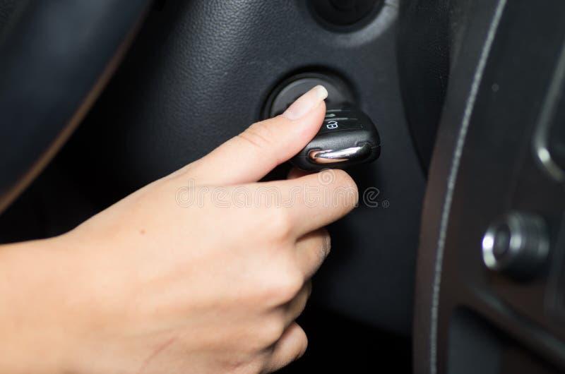 Plan rapproché à l'intérieur du véhicule de la main jugeant l'allumage, le volant et le fond intérieur noir, conducteur femelle photos stock
