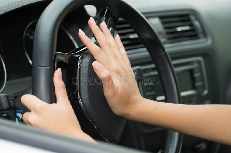 Plan rapproché à l'intérieur du véhicule de la main poussant sur le volant cornant le klaxon, fond intérieur noir, concept femell photographie stock