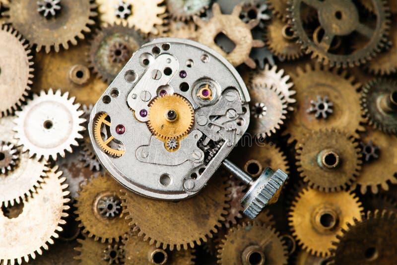Plan rapproché âgé de mécanisme d'horloge La rétro main observe des parties sur le fond de vitesses de bronze images libres de droits