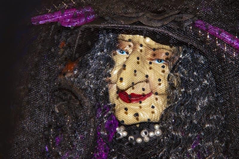 Plan rapproché élégant de visage de sorcière de décoration de Halloween vieux sous un voile et un rouge à lèvres de perle et roug photos stock