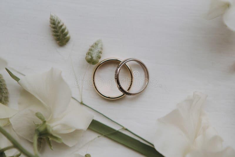 Plan rapproché aérien tiré des anneaux de mariage sur une surface blanche décorée des fleurs blanches et vertes photographie stock libre de droits