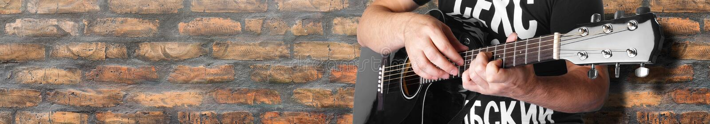 plan rapproché acoustique électrique noir de mur de briques de la corde 7maj5 de joueur de guitare vieux image libre de droits