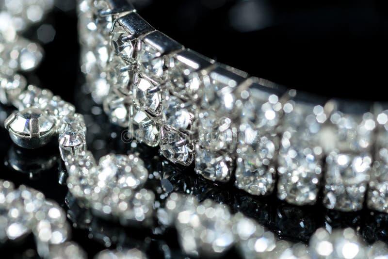 Plan rapproché argenté de bracelet et de collier de diamants sur un fond noir photos stock
