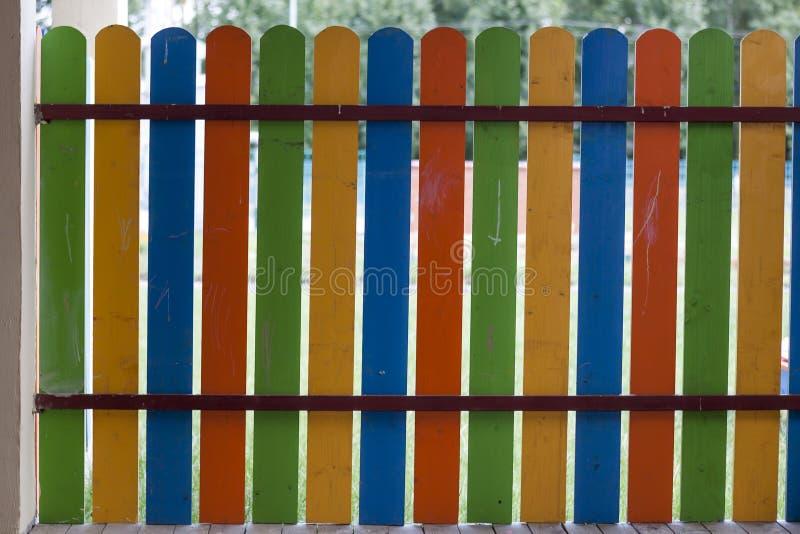 Plan rapproché basse de barrière décorative en bois multicolore bleue, verte, jaune et orange colorée lumineuse dehors le jour en photos libres de droits