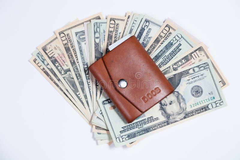 Plan rapproché beaucoup de billets de banque américains du dollar dans la fan, petit portefeuille brun en cuir fermé avec le bout photos libres de droits