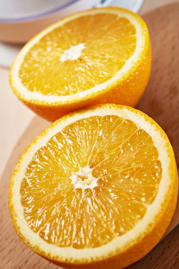 Plan rapproché bissecté juteux d'oranges sur la verticale de conseil en bois image stock