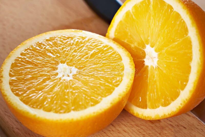 Plan rapproché bissecté juteux d'oranges sur le conseil en bois photos stock