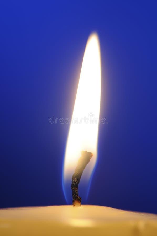 Plan rapproché brûlant de flamme de bougie sur le fond bleu images stock