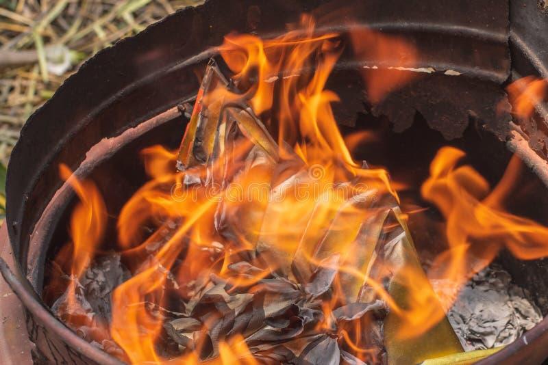 Plan rapproché brûlant le papier de Joss ou le billet de banque d'enfer pour des ancêtres image stock