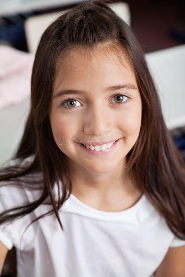 Plan rapproché d'écolière souriant dans la salle de classe photo libre de droits