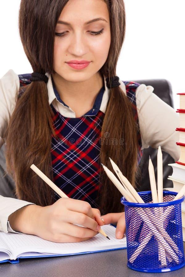 Plan rapproché d'étudiant se reposant à son bureau concentré et faisant h photo stock