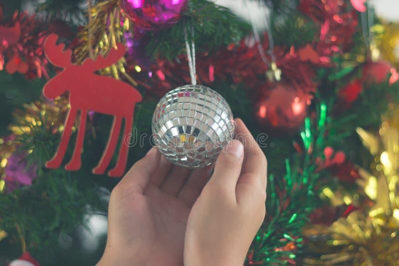Plan rapproché d'enfant accrochant la boule décorative de jouet sur l'arbre de Noël images libres de droits