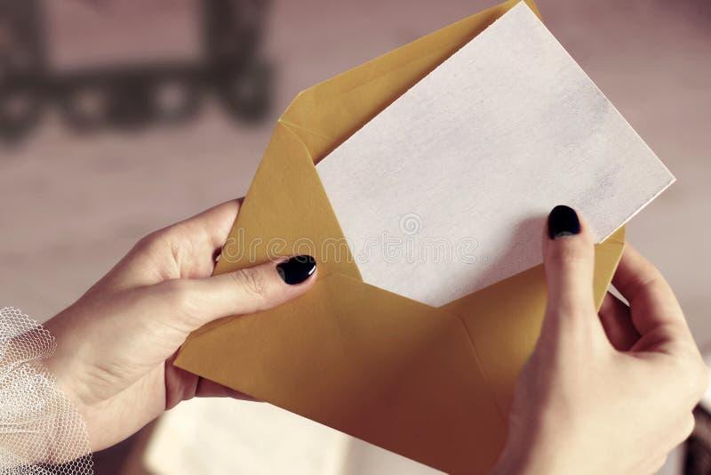 Plan rapproché d'enveloppe d'ouverture de main de femme avec la carte de visite professionnelle de visite de maquette ou de lettr photographie stock