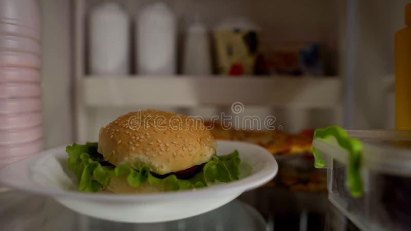 Plan rapproché d'hamburger dans le réfrigérateur, concept de nourriture industrielle, nutrition malsaine, calories image libre de droits