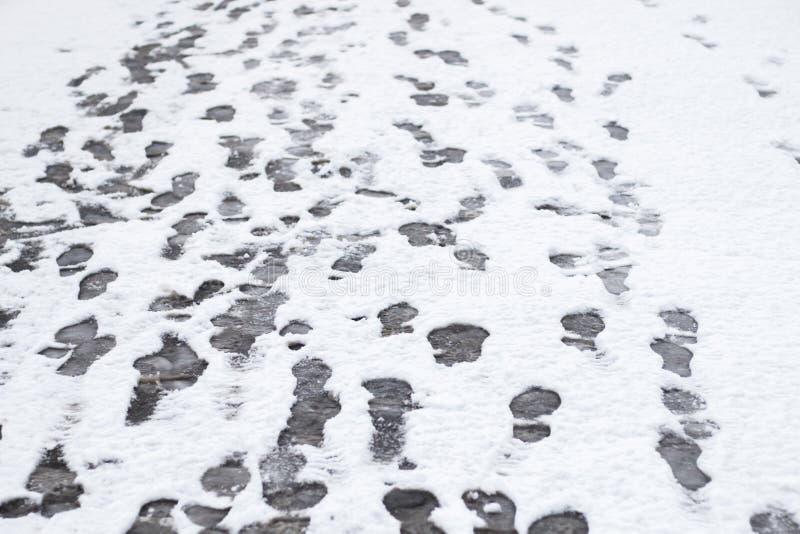 Plan rapproché d'hiver de beaucoup de footstprints dans la neige fraîchement tombée photos stock