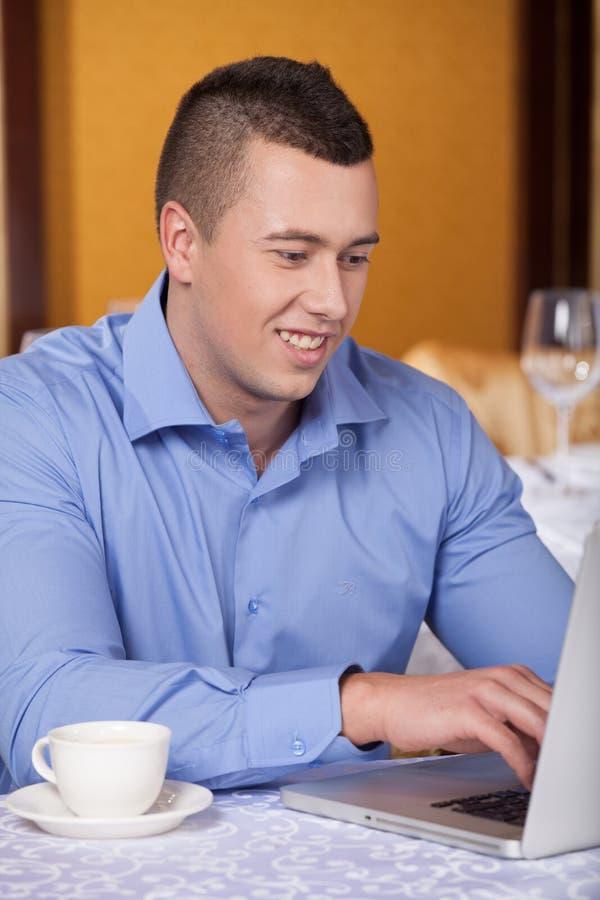 Plan rapproché d'homme bel se reposant en café et café potable photographie stock