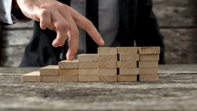 Plan rapproché d'homme d'affaires marchant ses doigts vers le haut des étapes en bois photos libres de droits