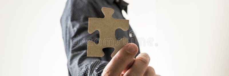Plan rapproché d'homme d'affaires tenant un morceau vide de puzzle vers vous image stock