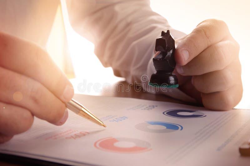 Plan rapproché d'homme d'affaires travaillant avec le graphique de document et tenant une pièce d'échecs photographie stock libre de droits