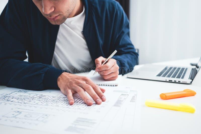 Plan rapproché d'ordinateur portable d'utilisations d'architecte de mains et de modèle de construction sur la table de fonctionne images stock