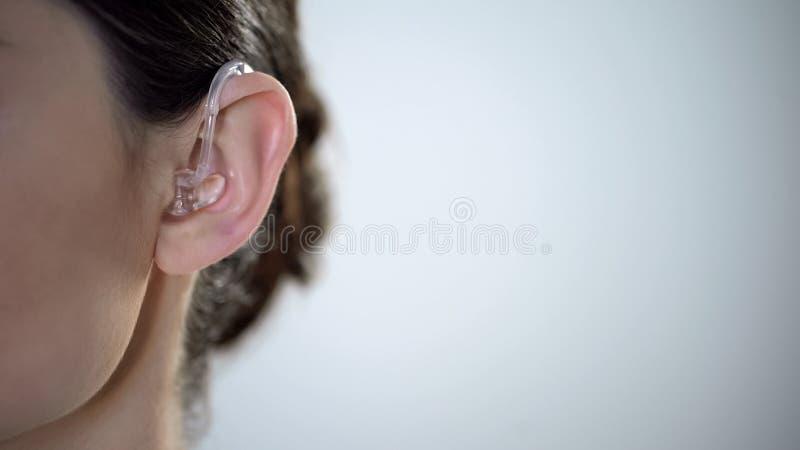 Plan rapproché d'oreille à la prothèse auditive, jeune femme sourde s'ajustant sur l'environnement photos stock