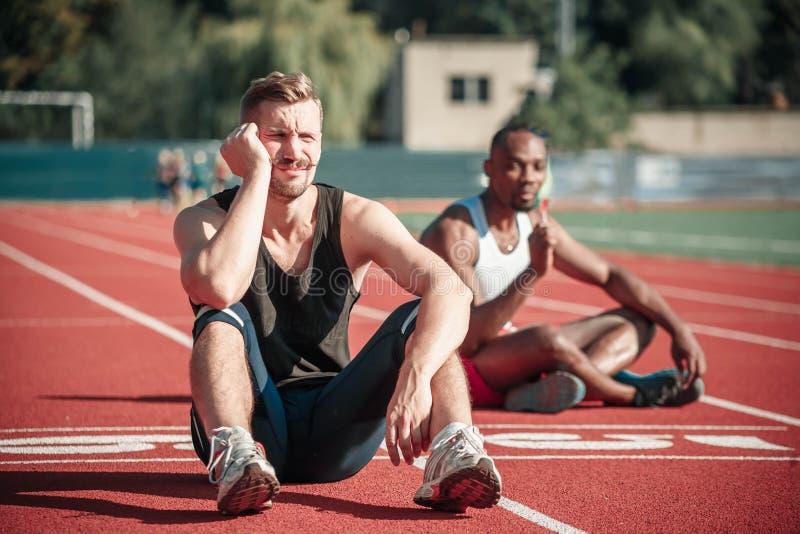 Plan rapproché d'un athlète masculin triste s'asseyant sur un joyeux fond photos libres de droits
