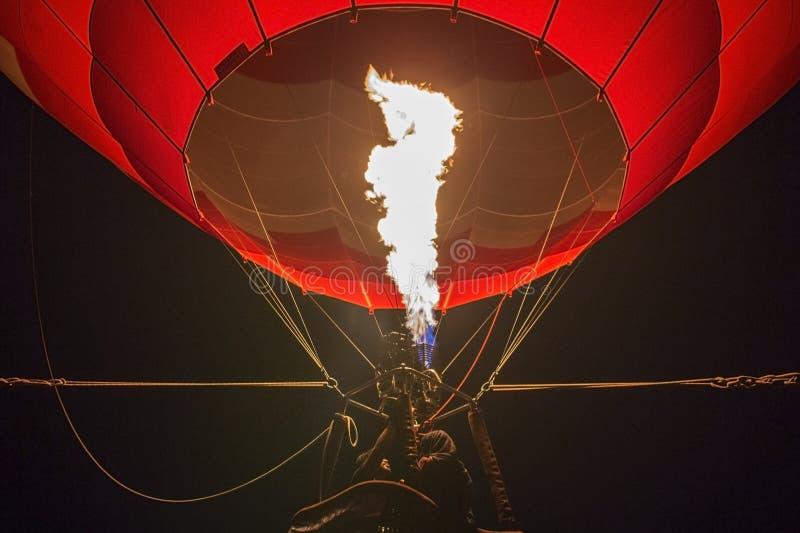 Plan rapproché d'un ballon à air chaud gonflé avec le feu rougeoyant la nuit pendant un festival d'airshow images libres de droits