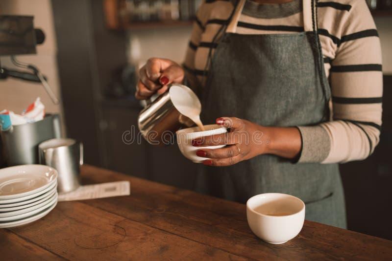 Plan rapproché d'un barman africain faisant une tasse du cappuccino photos libres de droits