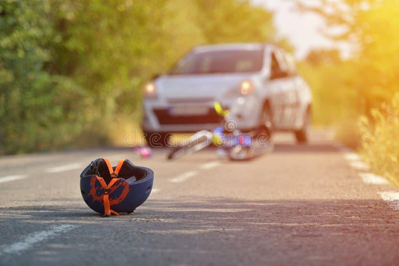 Plan rapproché d'un casque allant à vélo tombé sur l'asphalte à côté d'un b photos libres de droits
