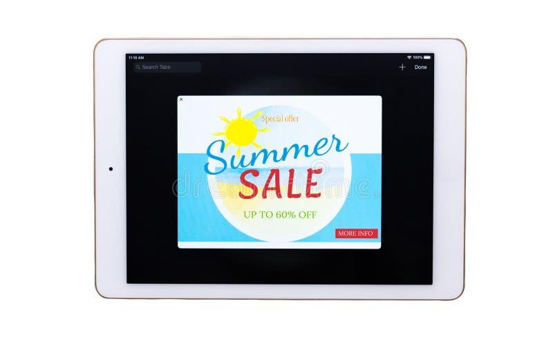 Plan rapproché d'un comprimé numérique avec la bannière d'offre de vente sur un écran sur le fond blanc photos stock