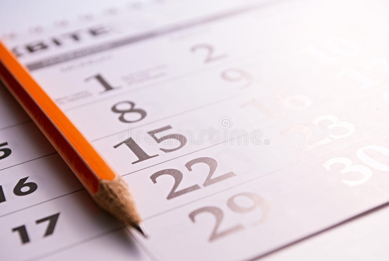 Plan rapproché d'un crayon à la page d'un calendrier image stock