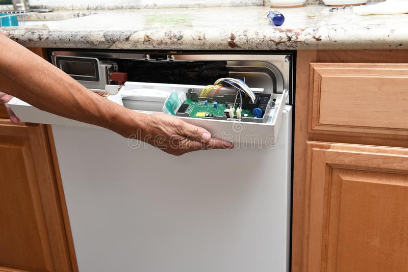 Plan rapproché d'un dépanneur d'appareils enlevant le panneau de commande sur un lave-vaisselle cassé photographie stock libre de droits