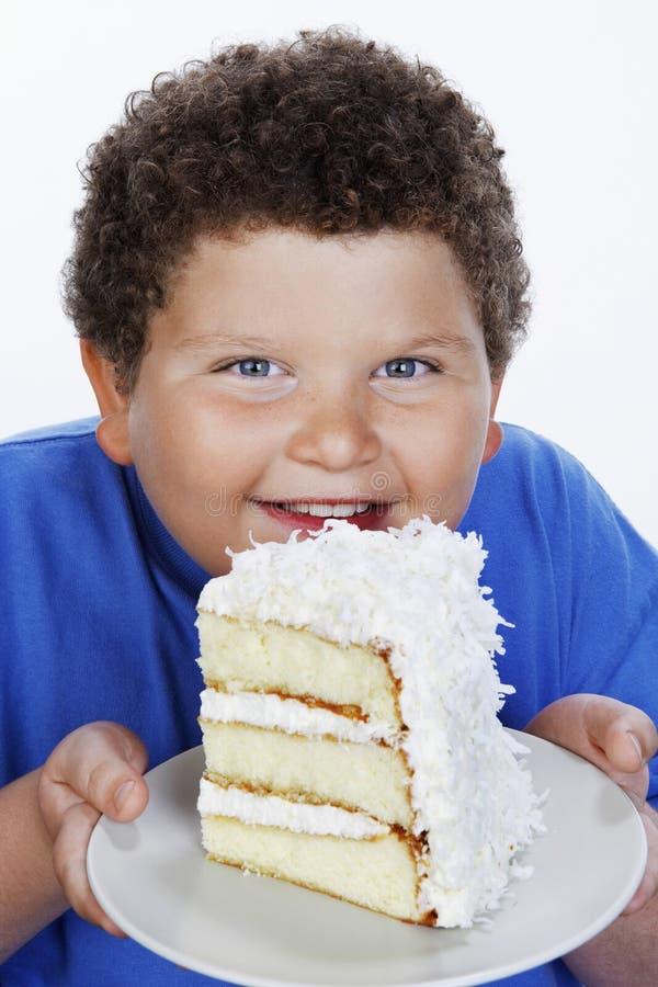 Plan rapproché d'un garçon de poids excessif tenant la grande tranche de gâteau photos stock