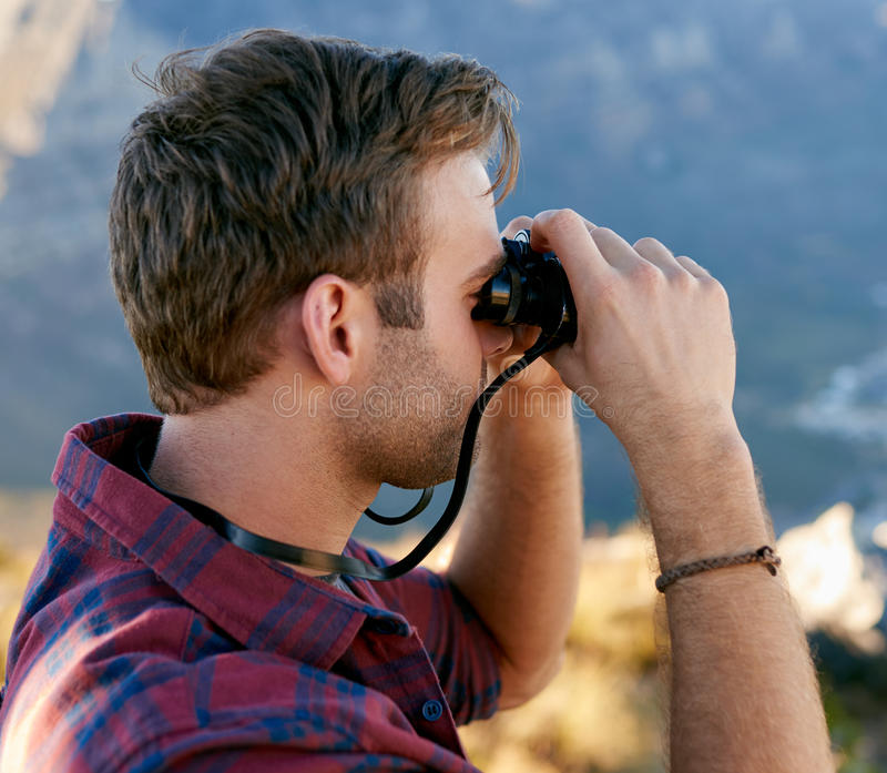 Plan rapproché d'un jeune homme dehors en nature utilisant des jumelles images stock