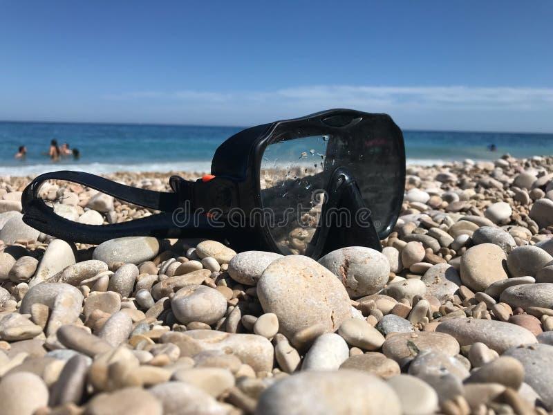 Plan rapproché d'un masque de plongée sur les pierres d'une plage image stock