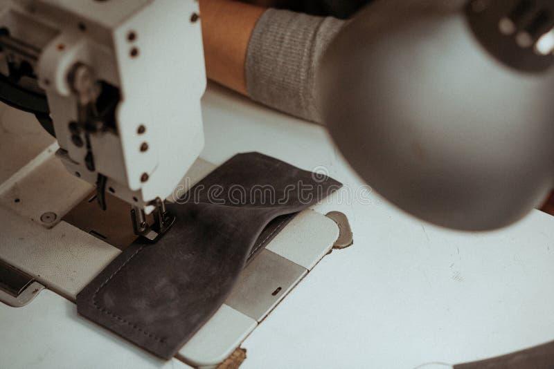 Plan rapproché d'un morceau de cuir se trouvant sur une machine à coudre sur la table dans l'atelier Maître fait main au travail  images stock