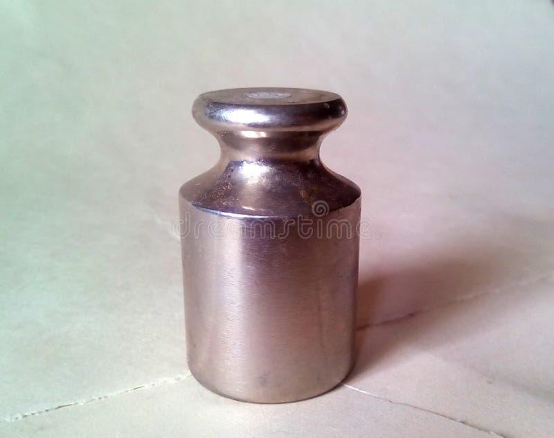 Plan rapproché d'un petit poids en métal pour des échelles Métal argenté léger sur un fond clair image stock