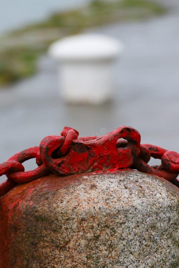 Plan rapproché d'un pilier en pierre de barrière et d'une chaîne rouge sur une pierre, copyspace photographie stock