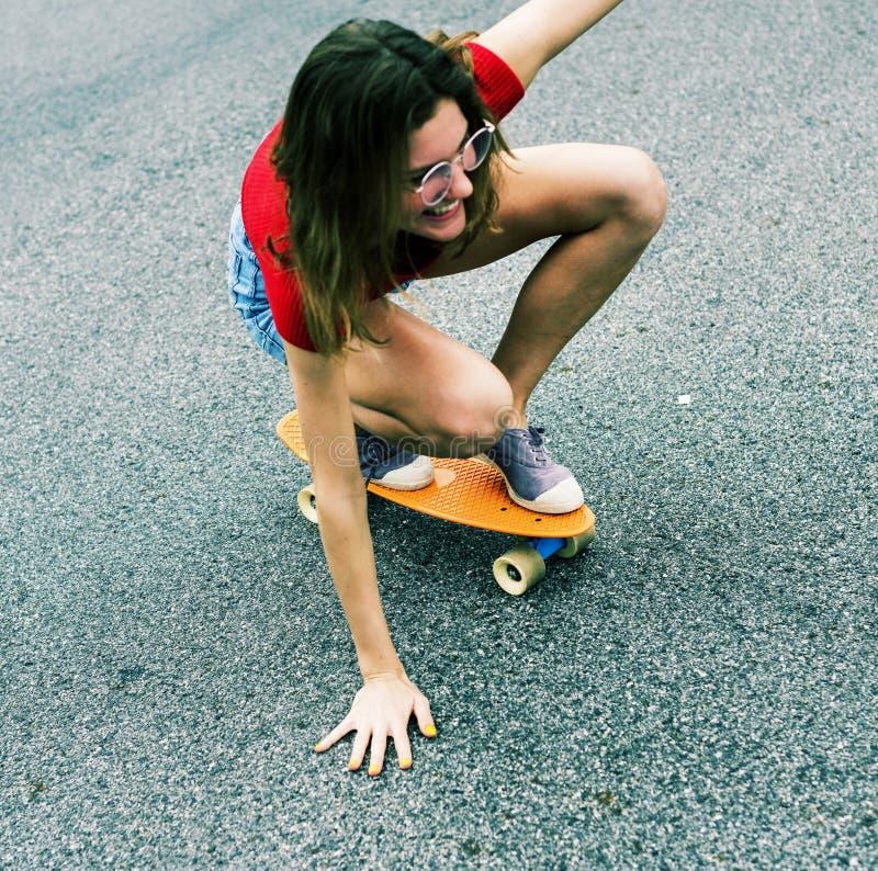 Plan rapproché d'un skateboarding caucasien de femme photo stock